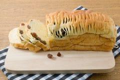 Pan cortado del pan de pasa en una tabla de cortar de madera Fotografía de archivo libre de regalías