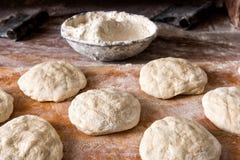 Pan crudo que sube en la tabla con el cuenco de harina Foto de archivo