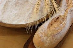 Pan crujiente del baguette con el tazón de fuente de madera de harina Imagen de archivo libre de regalías