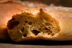 Pan crujiente francés, aislado en un fondo de madera del tablón Imagenes de archivo