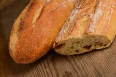 Pan crujiente francés, aislado en un fondo de madera del tablón Foto de archivo