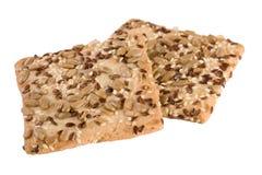 Pan curruscante con las semillas de las semillas del girasol, del lino y de sésamo en el fondo blanco Imagen de archivo libre de regalías