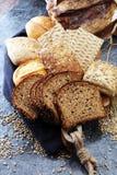 Pan de centeno cortado en tabla de cortar Pan de centeno del grano y rol enteros fotos de archivo