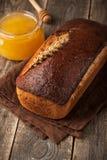 Pan de centeno hecho en casa y tarro de cristal de la miel en la tabla de madera Fotografía de archivo libre de regalías