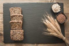 Pan de centeno integral de la aptitud Pan del pan de centeno cortado con las semillas en plato negro de la pizarra con el espacio fotos de archivo