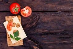 Pan de centeno, queso, tomate y perejil curruscantes en una tabla vieja Fotos de archivo libres de regalías