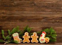Pan de jengibre: calcetín, gallo, hombres de pan de jengibre rama del Piel-árbol contra la perspectiva de una pared de madera Fotos de archivo libres de regalías