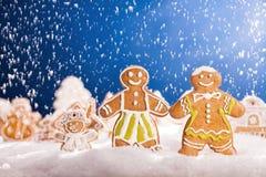 Pan de jengibre de la Navidad con nieve que cae Imágenes de archivo libres de regalías