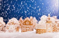 Pan de jengibre de la Navidad con nieve que cae Imagen de archivo