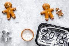 Pan de jengibre del cocinero por el Año Nuevo 2018 Hombre de pan de jengibre, harina en la opinión superior del fondo de piedra Foto de archivo libre de regalías