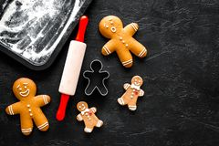 Pan de jengibre del cocinero por el Año Nuevo 2018 Hombre de pan de jengibre, rodillo, harina en copyspace negro de la opinión su Imagen de archivo libre de regalías