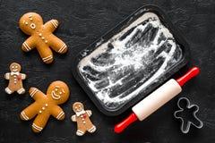 Pan de jengibre del cocinero por el Año Nuevo 2018 Hombre de pan de jengibre, rodillo, harina en maqueta negra de la opinión supe Foto de archivo