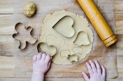 Pan de jengibre del corte de los moldes de metal por las manos de los niños Fotografía de archivo