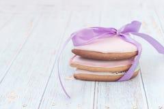 Pan de jengibre del rosa en forma de corazón Estilo elegante lamentable En un fondo ligero del pueblo foto de archivo