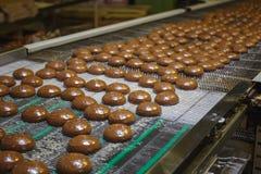 Pan de jengibre en vías del satinado en la banda transportadora Fábrica de la confitería Cadena de producción de las galletas de  imagen de archivo libre de regalías