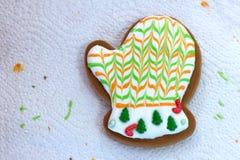 Pan de jengibre hecho en casa de la Navidad adornado bajo la forma de manoplas en el fondo de una servilleta blanca con los resto Imágenes de archivo libres de regalías