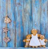 Pan de jengibre, hombres de pan de jengibre en el fondo de madera azul, tarjeta de felicitación de la plantilla Imagen de archivo libre de regalías