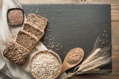 Pan de la aptitud Un pan del pan de centeno entero rústico fresco con trigo, cortado en un plato y un tablero negros de la pizarr Foto de archivo libre de regalías