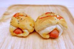 Pan de la salchicha con la salsa de tomate en madera del plato Foto de archivo