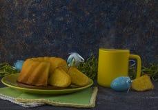 Pan de Pascua en la placa verde, la taza amarilla y los huevos de Pascua pintados fotos de archivo