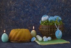 Pan de Pascua y huevos de Pascua azules en una cesta en la tabla de piedra oscura foto de archivo