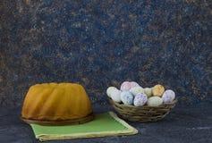 Pan de Pascua y mini huevos de Pascua en una pequeña cesta en la tabla de piedra oscura fotos de archivo