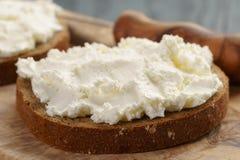 Pan de Rye con el queso cremoso en la tabla de madera Foto de archivo libre de regalías