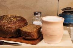 Pan de Rye con la sal en una tabla de cortar, el pote de arcilla con leche y una linterna de keroseno Foto de archivo libre de regalías