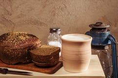 Pan de Rye con la sal en una tabla de cortar, el pote de cerámica con leche y una linterna de keroseno Foto de archivo