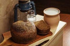 Pan de Rye con la sal en una tabla de cortar, pote de cerámica con leche Imagenes de archivo