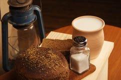 Pan de Rye con la sal en una tabla de cortar, un pote de leche y una linterna de keroseno Fotografía de archivo libre de regalías