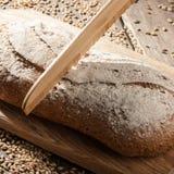 Pan de Rye con las semillas en una tabla de cortar, un cuchillo de madera imagen de archivo