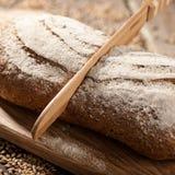 Pan de Rye con las semillas en una tabla de cortar, un cuchillo de madera fotos de archivo