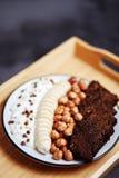 Pan de Rye, plátano, granos, avellana y yogur en una bandeja de madera ligera en fondo negro imágenes de archivo libres de regalías