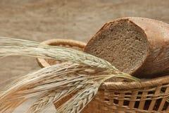 Pan de Rye y espigas de trigo en cesta Imagenes de archivo