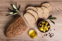 Pan del artesano con las aceitunas y el aceite de oliva en una tabla de madera fotografía de archivo