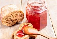 Pan del primer con la mermelada de fresa, cuchara de madera, tarro de atasco en la tabla de madera imagen de archivo libre de regalías