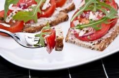 Pan del tomate con el pedazo en una fork Imagenes de archivo