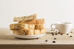 Pan del trigo con el sésamo, los granos de café y la taza de café blancos fotografía de archivo