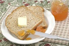 Pan del trigo integral con el atasco y la mantequilla del melocotón imagen de archivo libre de regalías