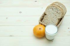Pan del trigo integral en cesta con la naranja y la leche Fotos de archivo libres de regalías