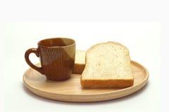 Pan del trigo y taza de café en un fondo blanco Imagen de archivo