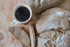 Pan del pan y de la taza de café recientemente cocidos hechos en casa en la tabla Fotografía de archivo libre de regalías