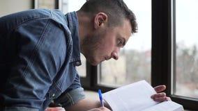 Pan des jungen Mannes studierend nahe dem Fenster stock video footage