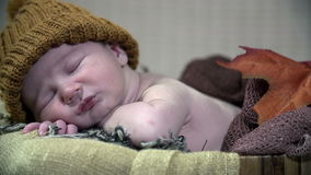 Pan detail shot of undressed baby with a brown hat stock video footage