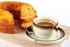 Pan di Spagna con la tazza di caffè ed il cucchiaio sulla zolla di legno Fotografia Stock