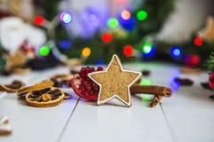 Pan di zenzero sotto forma di stelle, palle rosse di Natale, limoni secchi, cannella e ghirlanda e luci verdi Immagini Stock