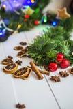 Pan di zenzero sotto forma di stelle, palle rosse di Natale, limoni secchi, cannella e ghirlanda e luci verdi Fotografia Stock