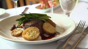 Pan down to a sun light steak meal stock footage