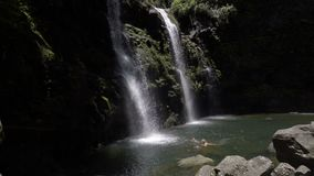 Pan down to tourists swiming in the Upper Waikani Falls. Slow pan down to tourists swiming in Upper Waikani Falls stock video footage